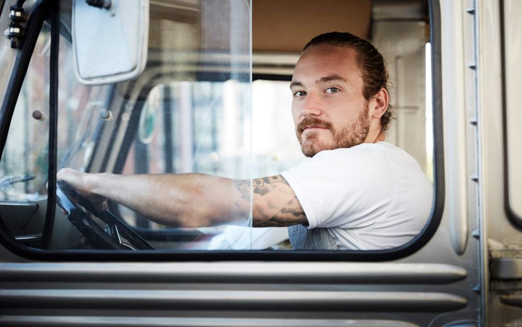 Mann sitter bak rattet i en lastebil
